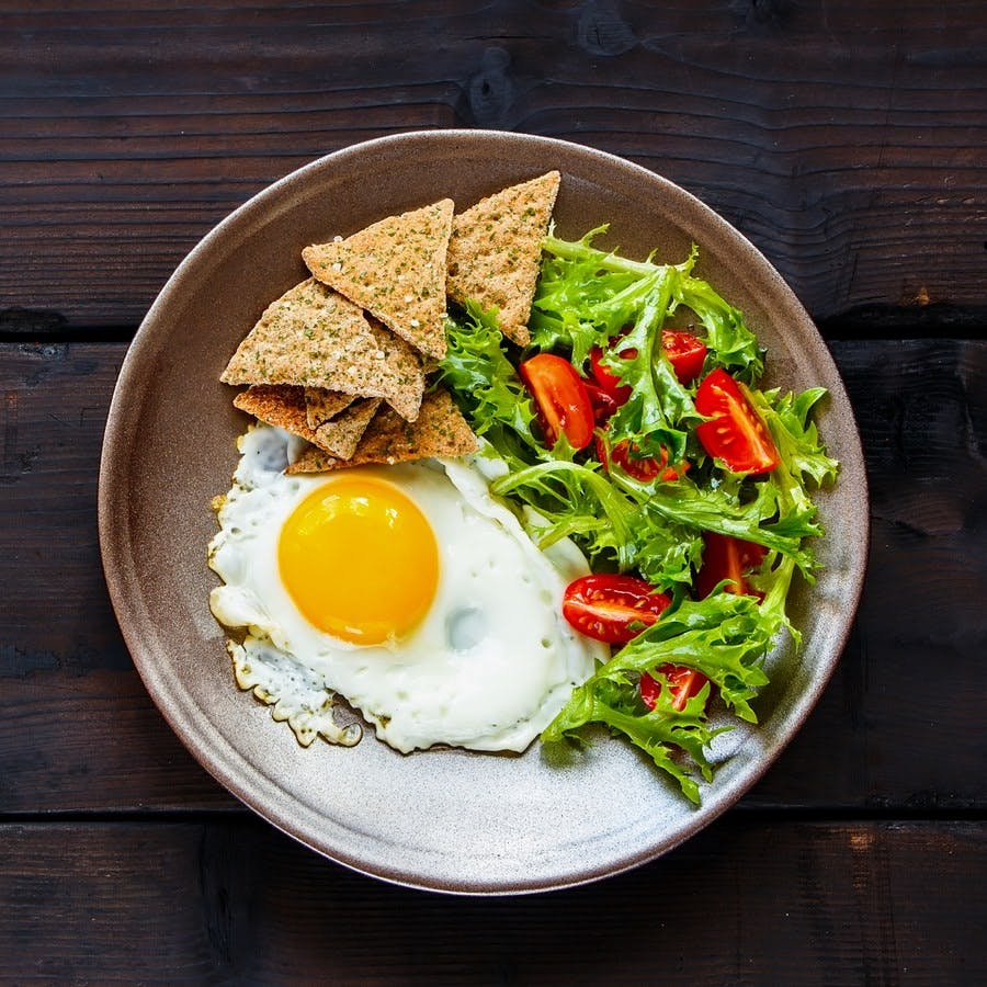 Healthy vegetarian breakfast flat-lay. Breakfast plate – cracker, arugula, cherry tomatoes and fried egg on dark wooden background, top view, copy space. Clean eating food concept