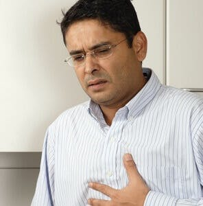 man with heartburn or stomach upset holding his chest