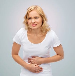 People, healthcare and problem concept – unhappy woman suffering from stomach ache over gray background