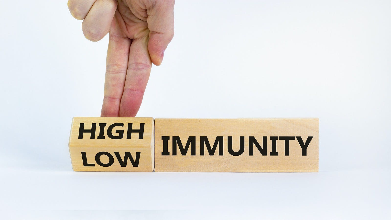 High or low immunity symbol. Doctor turns a block and changes words 'low immunity' to 'high immunity'. Beautiful white background. Medical, high or low immunity concept. Copy space.