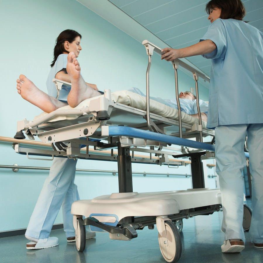 Nurses Moving Patient in Corridor