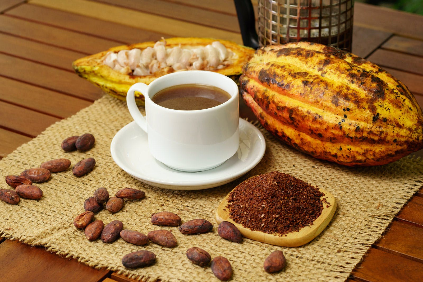 Hot brewed cacao drink, raw cocoa fruit, cacao beans, nibs on table