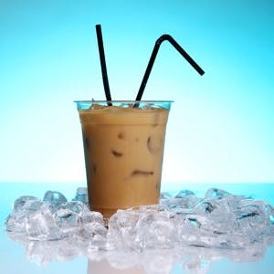 Cold coffee drink with ice on white background