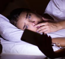 woman staring at cell phone in bed with anxious look on her face