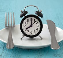 empty plate with a clock indicating intermittent fasting or time-restricted eating