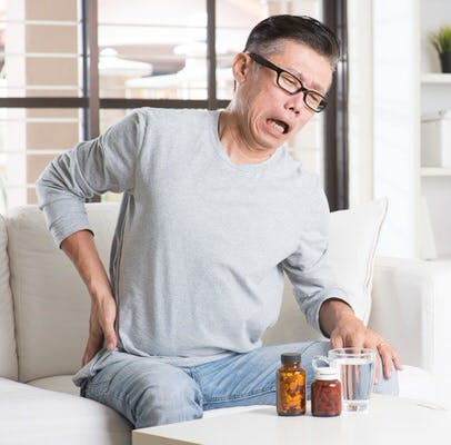 Portrait of casual 50s mature Asian man back pain, pressing on hip with painful expression, sitting on sofa at home, medicines and water on table.