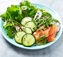 A low-carb mixed leaf salad with smoked salmon, spinach, cucumber and onions; eat to lower cholesterol