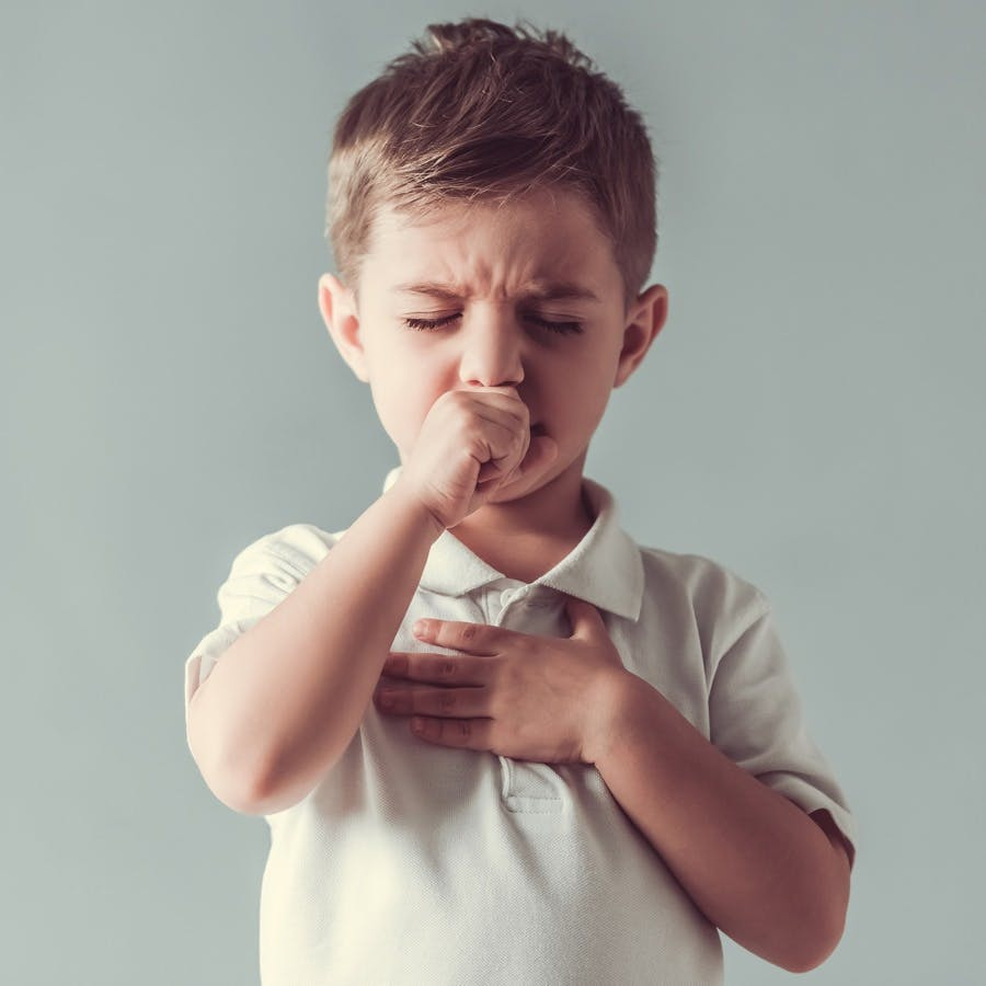 young boy coughing and holding chest