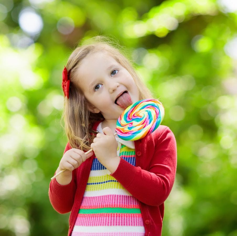 A little girl with a sweet tooth licking a lollipop