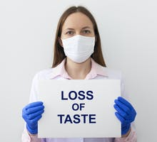 masked patient holding up sign saying loss of taste