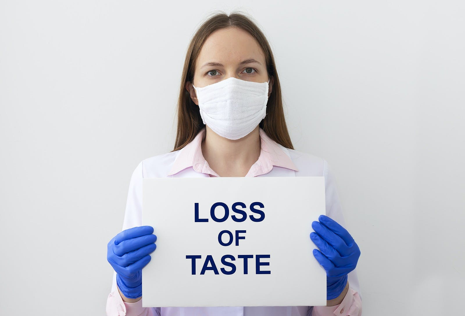 LOSS OF TASTE text as a symptom of disease. text on white paper in hands in protective gloves with doctor on white background