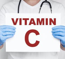 Male doctor holding a card that says vitamin C