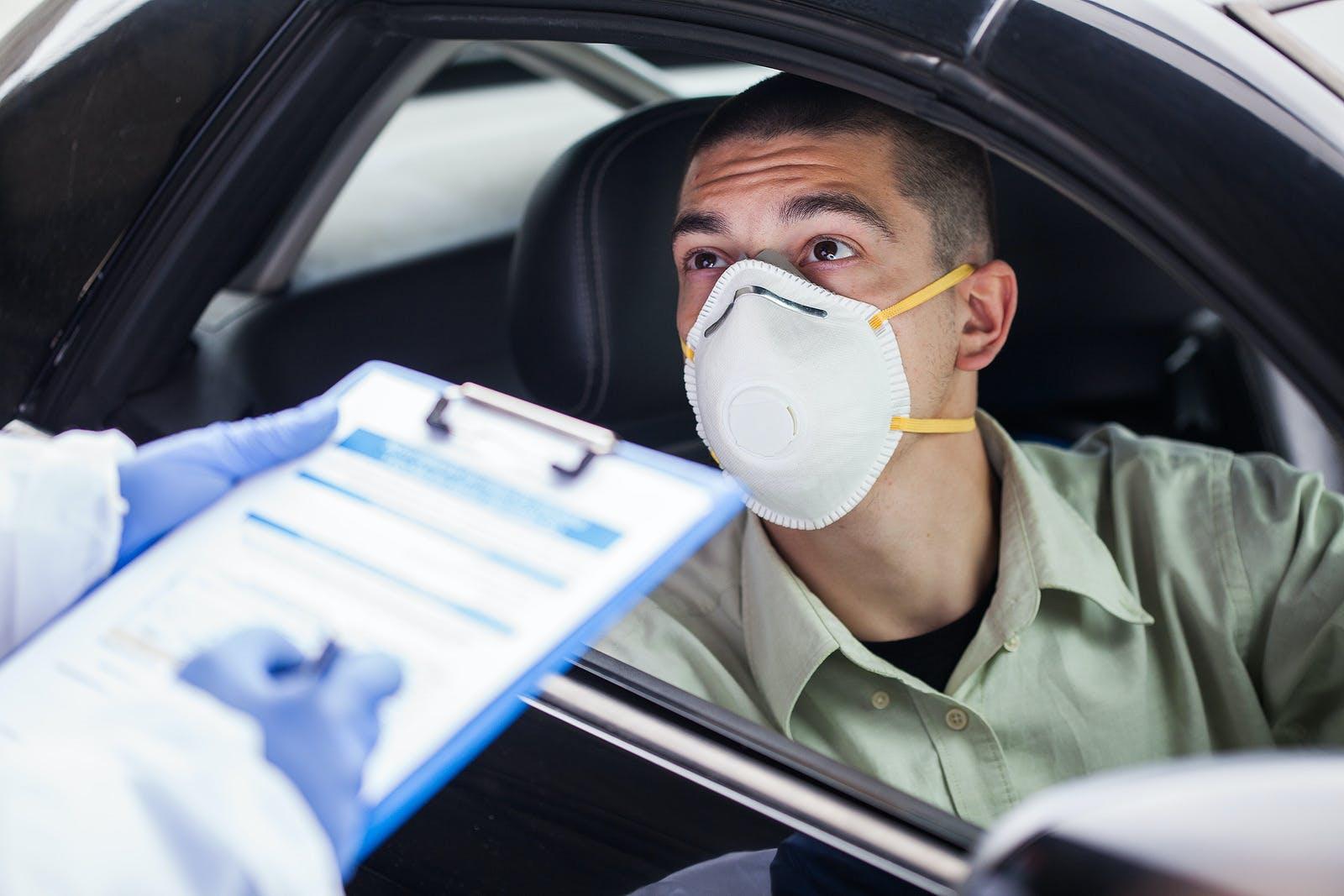 man in a car wearing an N-95 mask