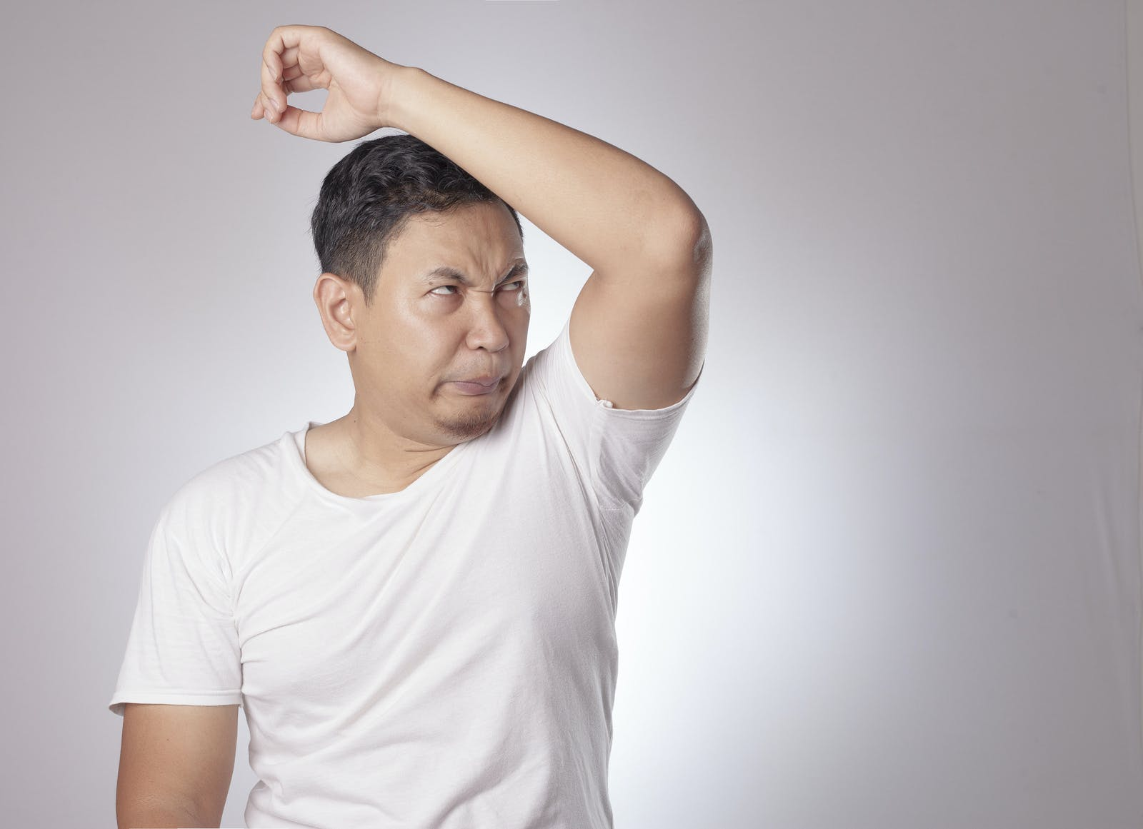 Man in T shirt sniffs his left armpit to see if he has horrible body odor