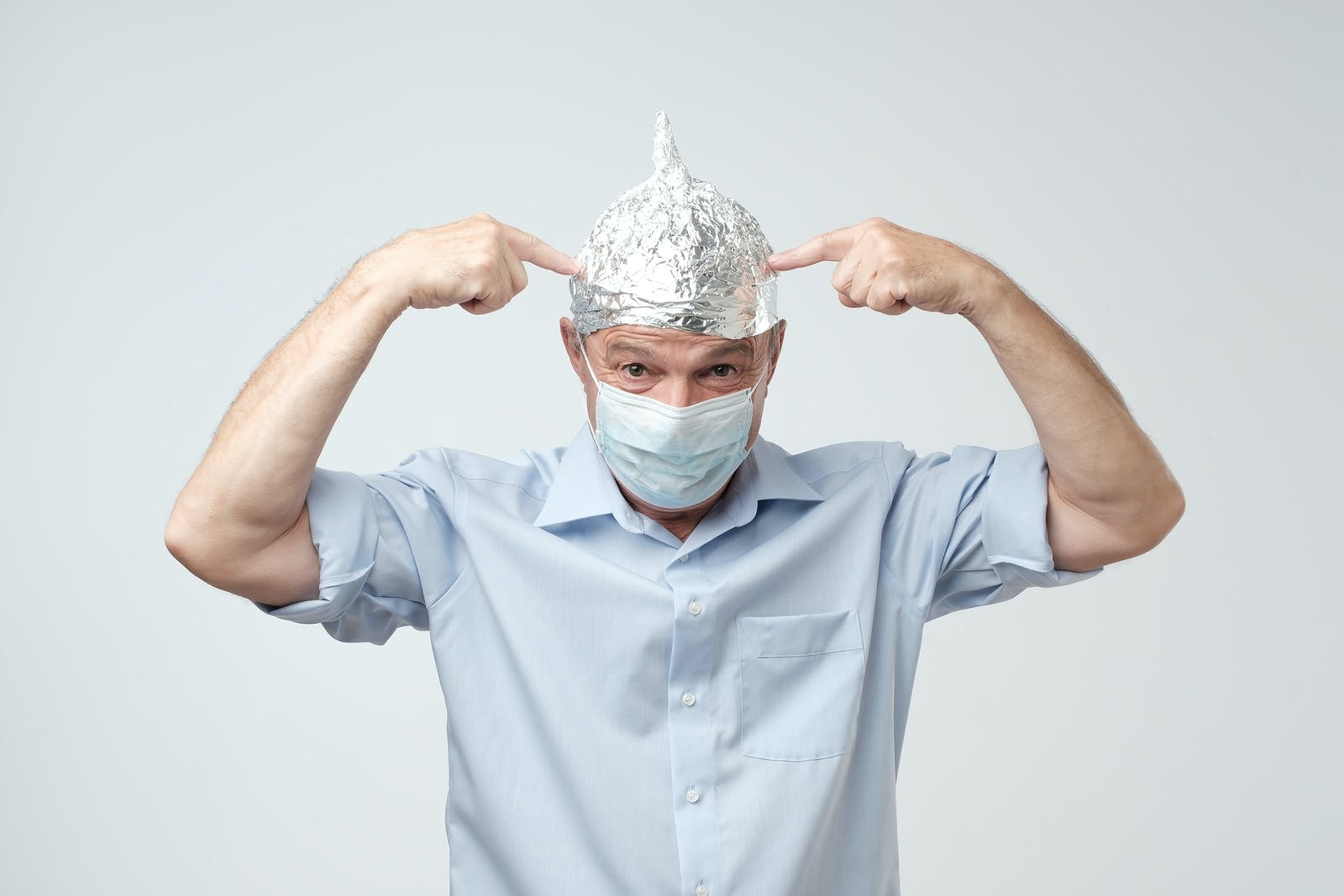 Caucasian mature man in a tin foil hat and medical hat displeased hiding from outdoor life.
