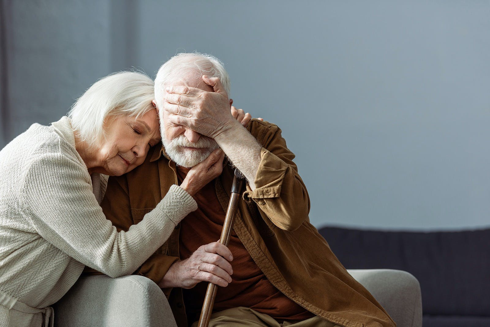 Senior man, sick on dementia, covering eyes with hand while wife embracing him with closed eyes