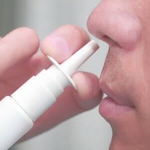 Man uses a nasal spray for treatment