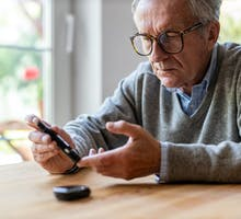 older man in sweater measures blood sugar to prevent diabetes