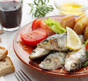 a plate with fish and veggies, typical mediterranean diet
