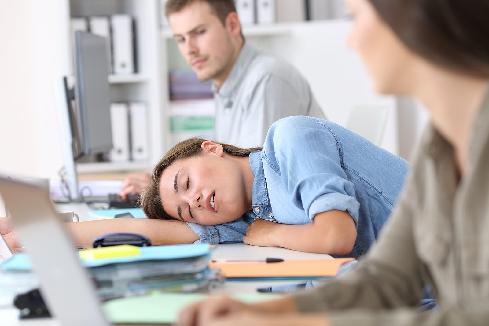 Fatigued employee sleeping on a desktop at office with her colleagues looking
