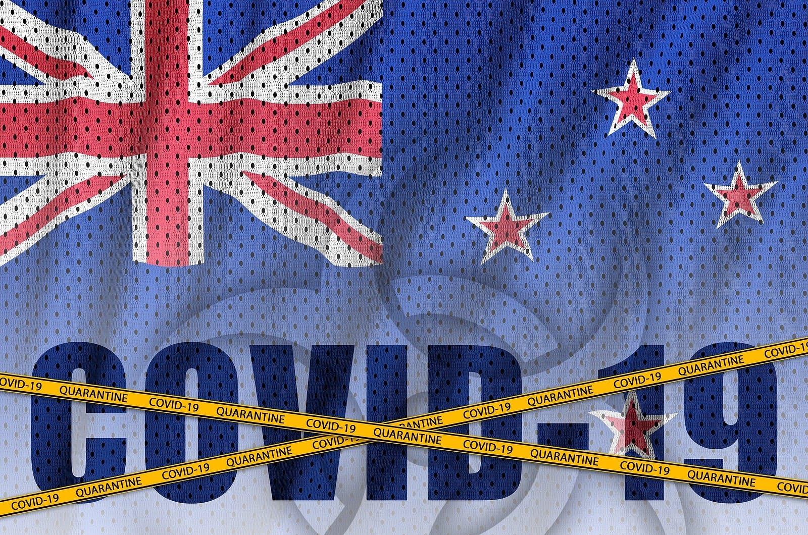 New Zealand flag and Covid-19 inscription with orange quarantine border tape. Coronavirus or 2019-nCov virus concept