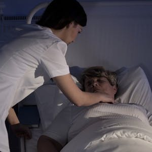 Night shift nurse helping a senior patient lying in hospital bed