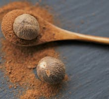 two whole nutmeg and powder in spoon