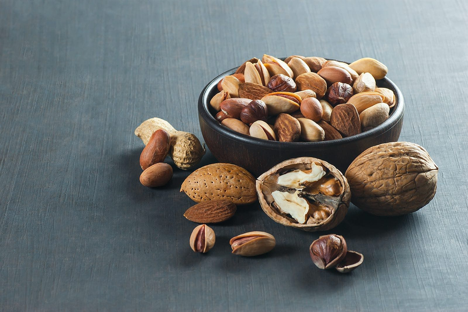 Nuts mix dried fruits in bowl, different kind of nut, healthy food on wooden table. Walnut, hazelnut, pistachio, peanut, almond. Assorted nuts concept