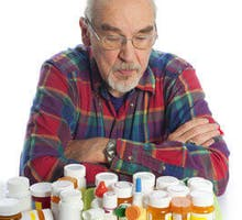 Senior Man, arms crossed, looks down at large assortment of prescription pill bottles