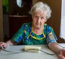 Older woman taking her blood pressure