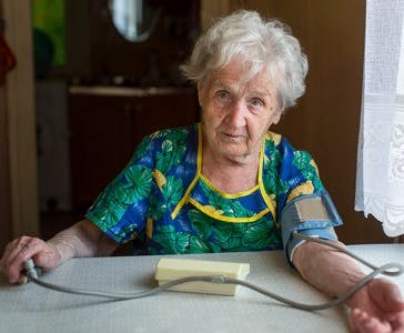 Elderly woman pensioner measures the blood pressure itself.