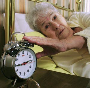older woman with insomnia silencing her alarm clock