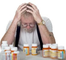 senior sitting behind a lot of pill bottles holding his head in his hands in confusion