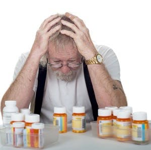 Senior sitting behind a lot of pill bottles holding his head in his hands isolated on white