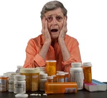 An elderly woman with dementia and a tableful of medications looking overwhelmed and confused