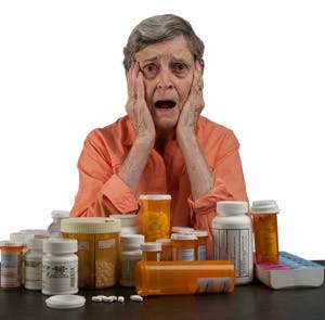 An elderly woman with a tableful of medications looking overwhelmed and confused