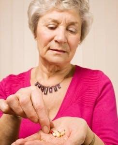 an older woman taking pills