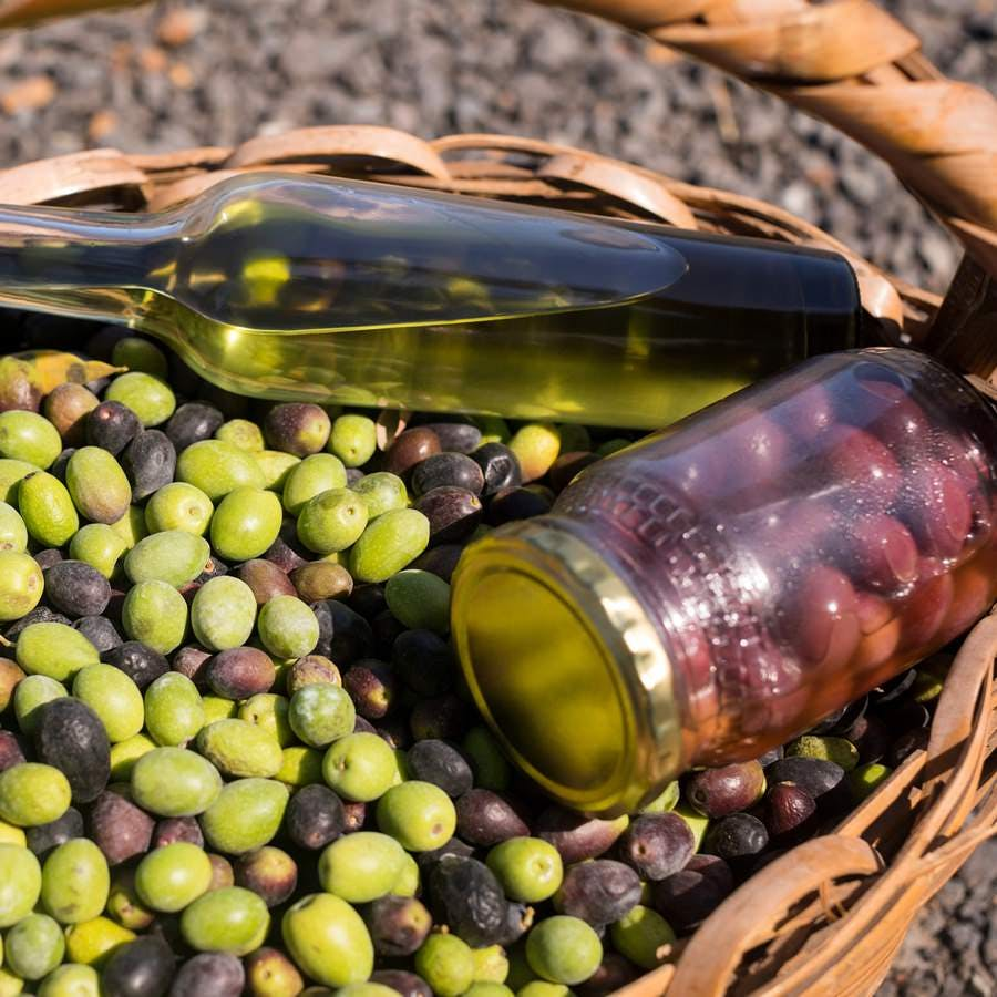 Close-up of olives, jar and olive oil bottle in basket on a sunny day