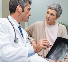 Male doctor and senior female patient discussing osteoporosis drug options