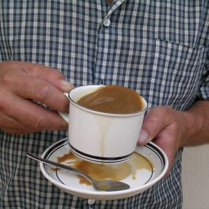 Person with Parkinson's disease spilling coffee from shaking