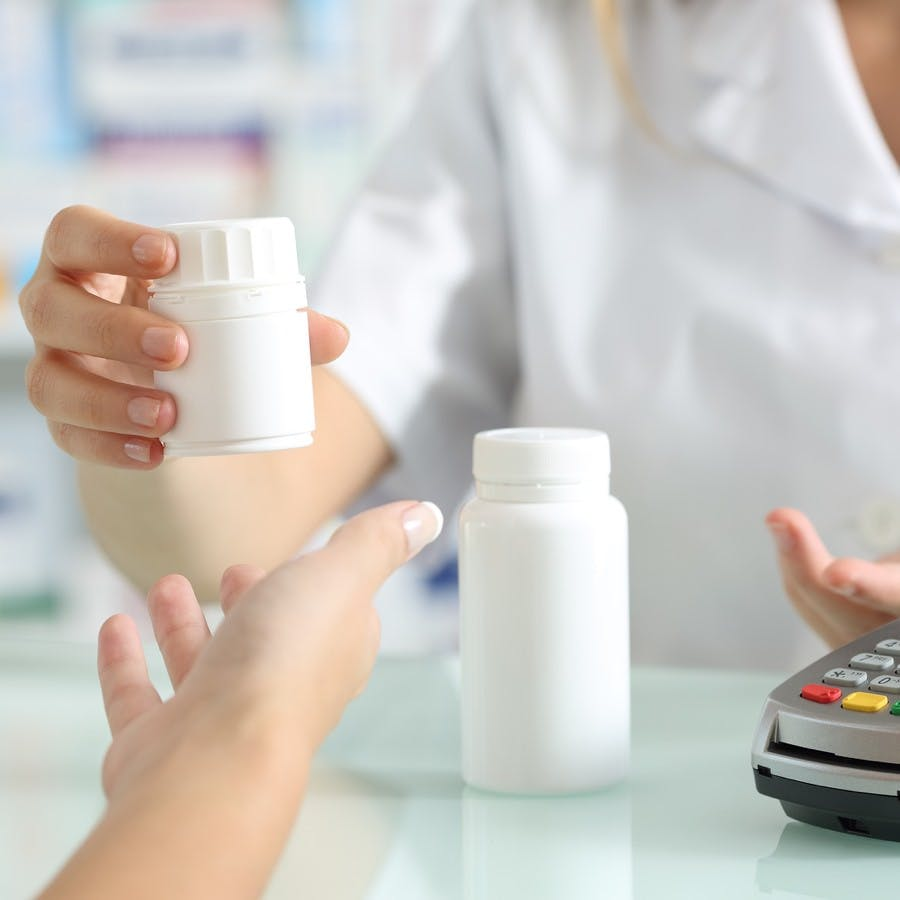 pharmacist hands selling medicines to a customer on a pharmacy desk