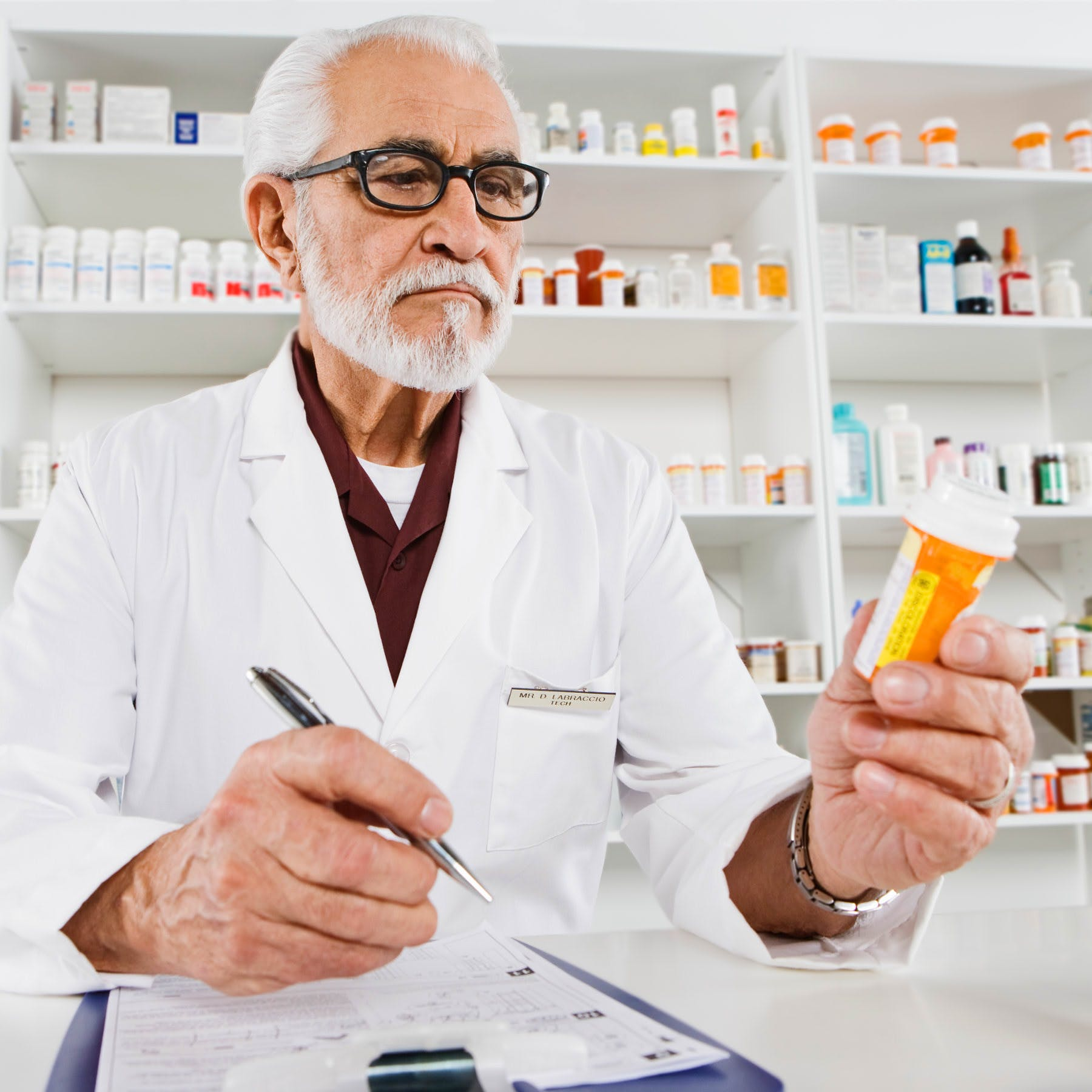 An older pharmacist reads a pill bottle