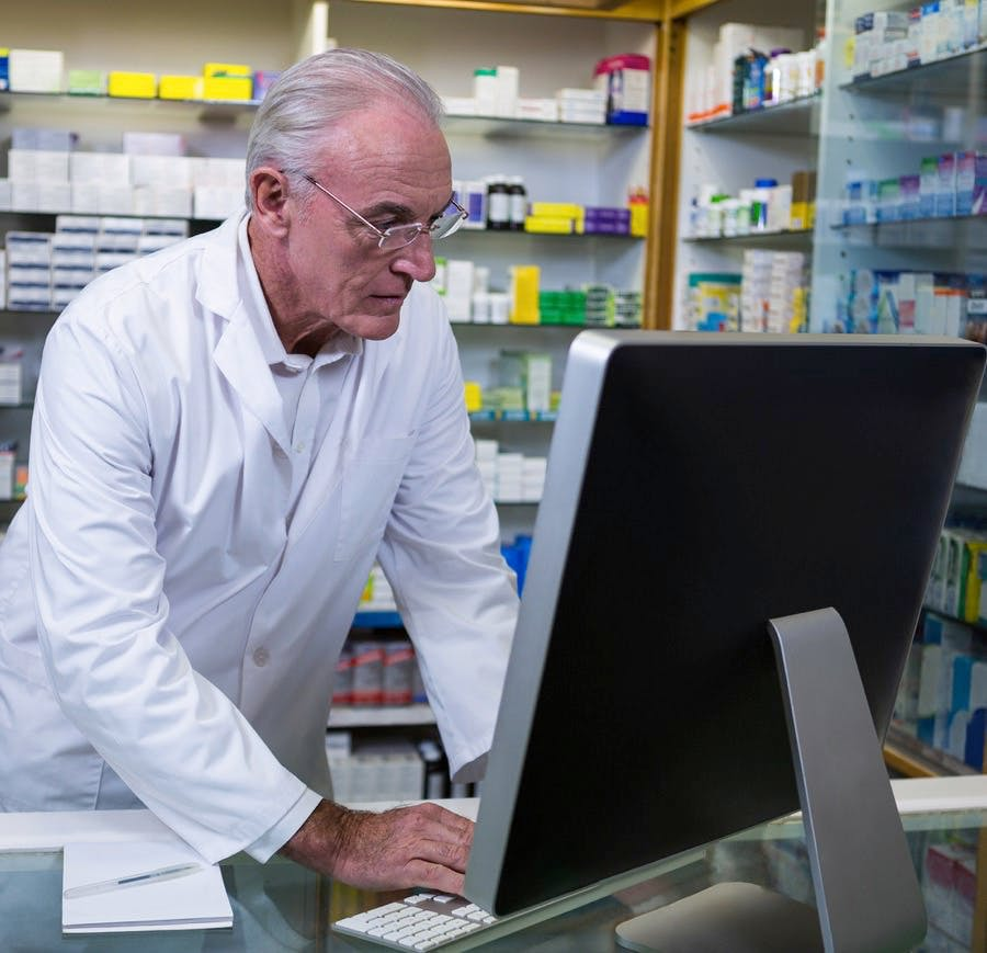 Older male pharmacist working on computer