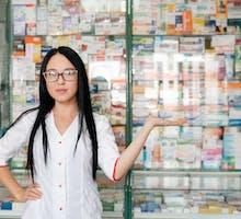 pharmacist in front of drug display as cheerleader for drugs