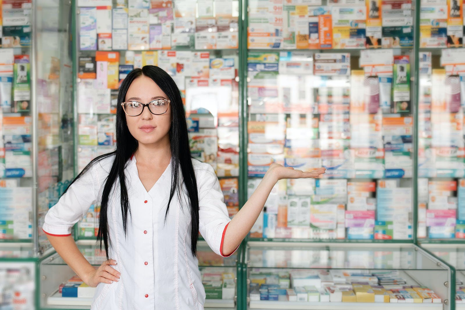 Pharmacy and pharmacist-seller. Female pharmacist with glasses posing on the background of shop Windows and pointing. Copy space