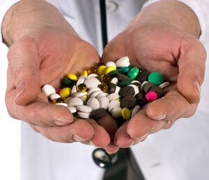 Two hands holding a variety of pill supplements