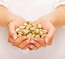 a woman holding a large handful of pistachio nuts