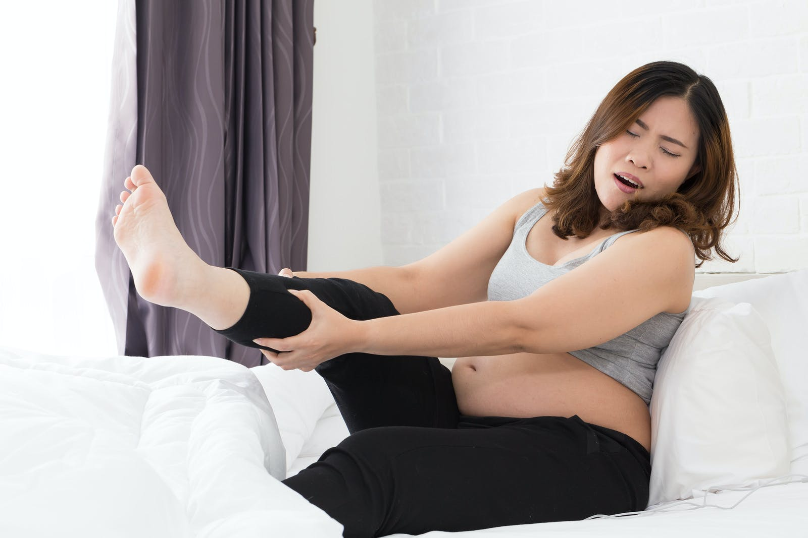 Pregnant women with cramp in leg on bed