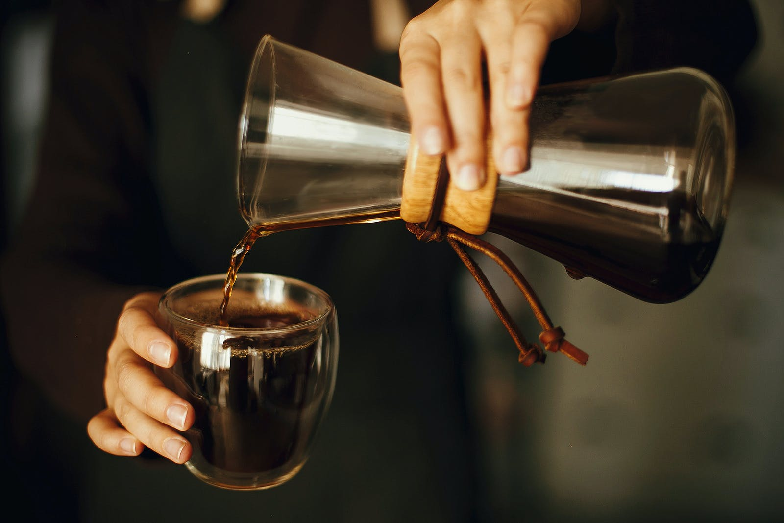 Professional female barista in black uniform making drip coffee. Person pouring fresh aromatic coffee from glass kettle in cup.  Alternative coffee brewing,