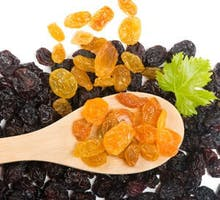 Wooden spoon with golden raisins on dark raisins